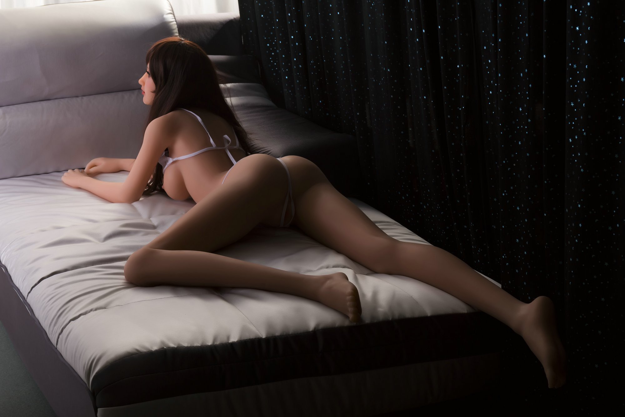 sex doll in sultry pose on bed