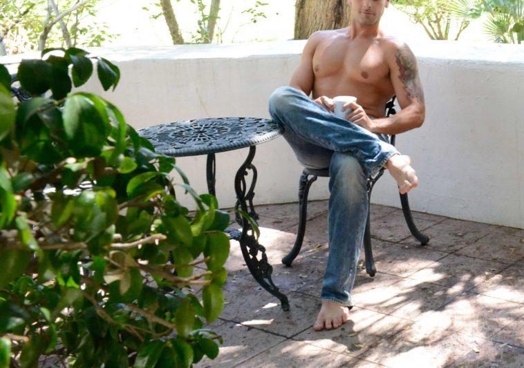 hot man sitting outside having a coffee