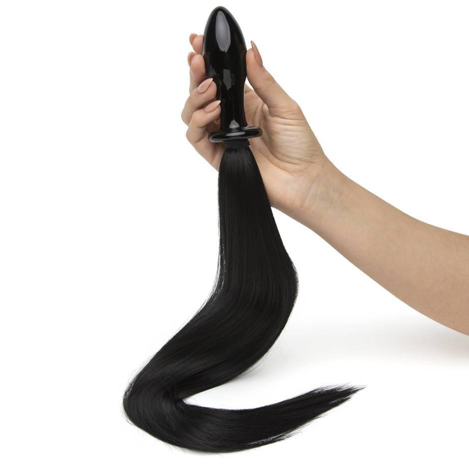 woman holding pony tail butt plug